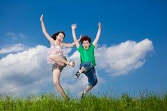 τα μπλε μάτια αγοριών στρέφουν τον ουρανό άλματος κοριτσιών χαμογελώντας μαλακό κατώτερο στοκ φωτογραφίες
