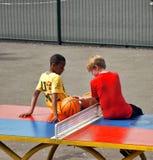 Τα νέα αγόρια κάθονται σε έναν πίνακα επιτραπέζιας αντισφαίρισης στοκ φωτογραφίες