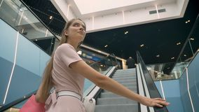 Τα νέα ελκυστικά κορίτσια που στέκονται στην κυλιόμενη σκάλα στη λεωφόρο, κρατώντας τις τσάντες, έννοια αγορών, διαμορφώνουν την  φιλμ μικρού μήκους