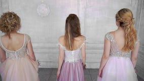 Τα νέα ενήλικα κορίτσια πηγαίνουν γύρω από το άσπρο δωμάτιο με τις πλάτες και τη στροφή τους στη κάμερα φιλμ μικρού μήκους
