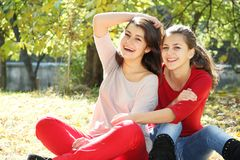 Τα νέα ευτυχή κορίτσια το φθινόπωρο σταθμεύουν το υπαίθριο πορτρέτο Στοκ Φωτογραφίες