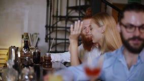 Τα νέα ζεύγη beautifil που κάθονται σε έναν φραγμό και πίνουν το κρασί και κοκτέιλ, έχουν τη διασκέδαση και τα φλερτ αυτή η νύχτα απόθεμα βίντεο