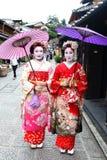 Τα νέα ιαπωνικά κορίτσια έντυσαν στη συνήθεια γκείσων ` s που παίρνει έναν περίπατο στους πέτρινος-στρωμένους δρόμους Ninenzaka κ στοκ εικόνα με δικαίωμα ελεύθερης χρήσης