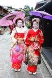 Τα νέα ιαπωνικά κορίτσια έντυσαν στη συνήθεια γκείσων ` s που παίρνει έναν περίπατο στους πέτρινος-στρωμένους δρόμους Ninenzaka κ στοκ φωτογραφίες με δικαίωμα ελεύθερης χρήσης