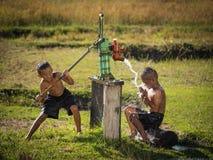 Τα νέα λικνίζοντας υπόγεια νερά αγοριών δύο λούζουν στις καυτές ημέρες Στοκ Φωτογραφίες