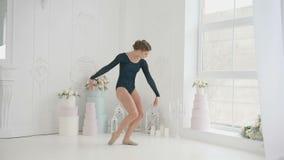 Τα νέα και όμορφα ballerinas προετοιμάζονται να χορεψουν δραστήρια, αλλά κομψός στα παπούτσια Pointe μπαλέτου της και στο Μαύρο φιλμ μικρού μήκους