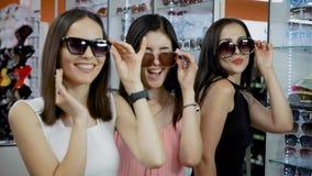 Τα νέα κορίτσια αγοράζουν τα γυαλιά ηλίου σε μια μικρή μπουτίκ απόθεμα βίντεο