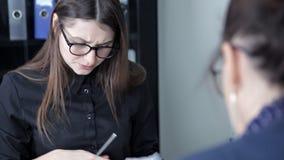 Τα νέα κορίτσια κάθονται στο γραφείο και συζητούν τα επιχειρηματικά σχέδια και τα νέα προγράμματα απόθεμα βίντεο