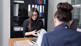 Τα νέα κορίτσια κάθονται στο γραφείο και συζητούν τα επιχειρηματικά σχέδια και τα νέα προγράμματα φιλμ μικρού μήκους