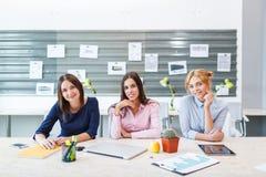 Τα νέα κορίτσια κάθονται στο γραφείο στον πίνακα Στοκ φωτογραφία με δικαίωμα ελεύθερης χρήσης
