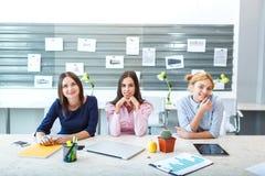 Τα νέα κορίτσια κάθονται στο γραφείο στον πίνακα Στοκ Εικόνες