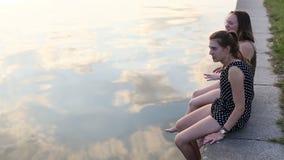 Τα νέα κορίτσια μιλούν ο ένας στον άλλο να καθίσουν στο ανάχωμα πετρών του ποταμού απόθεμα βίντεο