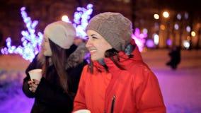 Τα νέα κορίτσια πίνουν τον καφέ το χειμώνα στο κέντρο της πόλης, κοντά στις χειμερινές διακοσμήσεις νέο έτος Χριστουγέννων απόθεμα βίντεο