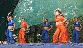 Τα νέα κορίτσια στο φωτεινό κοστούμι χορεύουν και παρουσιάζουν ακροβατικές ακροβατικές επιδείξεις στο Sc Στοκ φωτογραφίες με δικαίωμα ελεύθερης χρήσης