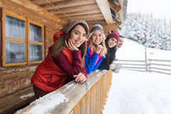 Τα νέα κορίτσια χειμερινό χιόνι εξοχικών σπιτιών πεζουλιών στο ξύλινο προσφεύγουν εξοχικό σπίτι Στοκ φωτογραφία με δικαίωμα ελεύθερης χρήσης