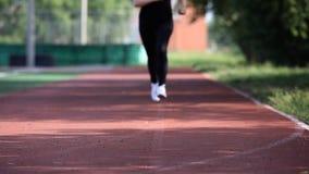 Τα νέα τρεξίματα γυναικών σε μια τρέχοντας διαδρομή Ξανθός φιλμ μικρού μήκους