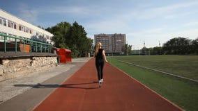Τα νέα τρεξίματα γυναικών σε μια τρέχοντας διαδρομή απόθεμα βίντεο