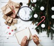 Τα νέα χέρια ατόμων έννοιας έτους σύνθεσης Χριστουγέννων γράφουν στο notepa Στοκ φωτογραφίες με δικαίωμα ελεύθερης χρήσης