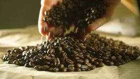 Τα νέα χέρια γυναικών με την όμορφη στιλβωτική ουσία καρφιών σύρουν μερικά ψημένα φασόλια καφέ απόθεμα βίντεο
