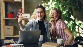 Τα νέα enterpreneurs μιλούν και κάνουν selfie με το έξυπνο τηλέφωνο καθμένος στο γραφείο στο σύγχρονο γραφείο Είναι απόθεμα βίντεο