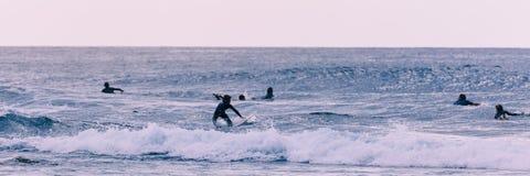 Τα νέα surfers παίρνουν τα κύματα, εκλεκτής ποιότητας ύφος στοκ εικόνα με δικαίωμα ελεύθερης χρήσης