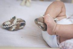 Τα νεογέννητα πόδια μωρών κλείνουν επάνω στις κάλτσες μαλλιού σε ένα άσπρο κάλυμμα Το μωρό είναι στο παχνί Μια κάλτσα αφαιρείται  στοκ φωτογραφία με δικαίωμα ελεύθερης χρήσης