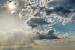 Τα νεφελώδη σύννεφα καλύπτουν τον ήλιο ακτίνες του φωτός στο πλούσιο σκοτεινό clou στοκ εικόνες