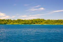 Τα νησιά Togian ταξιδεύουν τον προορισμό, τη φυσικές παραλία νησιών Togean και την ακτή με την πολύβλαστη πράσινη ζούγκλα στην τυ Στοκ Εικόνα