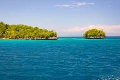 Τα νησιά Togian ταξιδεύουν τον προορισμό, τη φυσικές παραλία νησιών Togean και την ακτή με την πολύβλαστη πράσινη ζούγκλα στην τυ Στοκ εικόνα με δικαίωμα ελεύθερης χρήσης