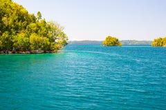Τα νησιά Togian ταξιδεύουν τον προορισμό, τη φυσικές παραλία νησιών Togean και την ακτή με την πολύβλαστη πράσινη ζούγκλα στην τυ Στοκ φωτογραφίες με δικαίωμα ελεύθερης χρήσης