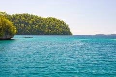 Τα νησιά Togian ταξιδεύουν τον προορισμό, τη φυσικές παραλία νησιών Togean και την ακτή με την πολύβλαστη πράσινη ζούγκλα στην τυ Στοκ Φωτογραφία