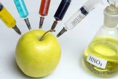 Τα νιτρικά άλατα, τα φυτοφάρμακα, τα μυκητοκτόνα και άλλες χημικές ουσίες εγχέονται σε ένα πράσινο μήλο με μια σύριγγα Η έννοια τ στοκ φωτογραφία