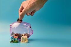 Τα νομίσματα πτώσης χεριών στη σαφή ρόδινα τράπεζα και το σπίτι Piggy διαμορφώνουν σύμφωνα με το μπλε Στοκ φωτογραφία με δικαίωμα ελεύθερης χρήσης