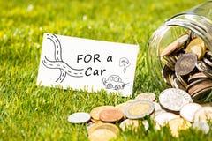 Τα νομίσματα στο βάζο γυαλιού για τα χρήματα στην πράσινη χλόη Στοκ Εικόνες