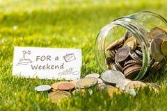 Τα νομίσματα στο βάζο γυαλιού για τα χρήματα στην πράσινη χλόη Στοκ Φωτογραφία