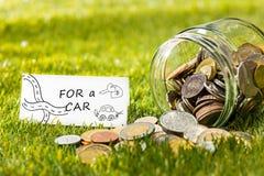 Τα νομίσματα στο βάζο γυαλιού για τα χρήματα στην πράσινη χλόη Στοκ Φωτογραφίες
