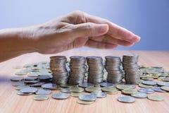 Τα νομίσματα σωρών με το χέρι της κάλυψης επιχειρηματιών συσσωρεύουν τα νομίσματα Στοκ Φωτογραφίες