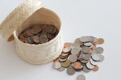 Τα νομίσματα χρημάτων τέθηκαν στην ύφανση καλαθιών στο άσπρο backg Στοκ Φωτογραφίες