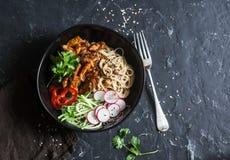 Τα νουντλς ρυζιού και το κοτόπουλο teriyaki ανακατώνουν τα τηγανητά με τα γρήγορα παστωμένα αγγούρια και τα ραδίκια Σε ένα σκοτει Στοκ Φωτογραφίες