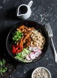 Τα νουντλς ρυζιού και το κοτόπουλο teriyaki ανακατώνουν τα τηγανητά με τα γρήγορα παστωμένα αγγούρια και τα ραδίκια Σε ένα σκοτει Στοκ Εικόνες