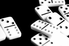 Τα ντόμινο είναι διεσπαρμένα σε μια σκοτεινή επιφάνεια μαύρο λευκό στοκ φωτογραφία