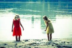 Τα ξανθά κορίτσια στο κόκκινο φόρεμα και το κίτρινο φόρεμα στον ποταμό προσαράσσουν Στοκ Εικόνες
