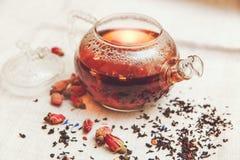 Τα ξηρά κόκκινα μικρά τριαντάφυλλα με το μαύρο τσάι Teapot γυαλιού, κατανάλωση τσαγιού, αρωματισμένα λουλούδια, λινό Tableclose Τ Στοκ Εικόνες
