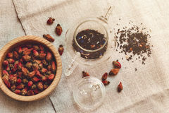 Τα ξηρά κόκκινα μικρά τριαντάφυλλα Teapot γυαλιού, κατανάλωση τσαγιού, παρουσιάζουν το τραχύ λινό Tableclose Πιάτο, που τονίζεται Στοκ εικόνα με δικαίωμα ελεύθερης χρήσης