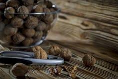 Τα ξύλα καρυδιάς είναι στον πίνακα δίπλα σε ένα κύπελλο των καρυδιών στοκ φωτογραφία με δικαίωμα ελεύθερης χρήσης