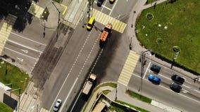 Τα οδικά μηχανήματα για τους δρόμους και τις εθνικές οδούς από το ρύπο, μεγάλα δύο πορτοκαλιά φορτηγά καθαρίζουν την οδική εναέρι φιλμ μικρού μήκους