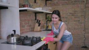 Τα οικιακά, εύθυμη θηλυκή νοικοκυρά στα λαστιχένια γάντια για τον καθαρισμό σκουπίζουν τα βρώμικα έπιπλα φιλμ μικρού μήκους
