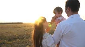 Τα οικογενειακά παιχνίδια με το μωρό στο ηλιοβασίλεμα Μπαμπάς και περίπατος Mom με την κόρη της στα όπλα της στο ηλιοβασίλεμα πατ απόθεμα βίντεο