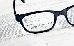 Τα οικονομικά νομίσματα διαγραμμάτων και γραφικών παραστάσεων βλέπουν μέσω του φακού γυαλιών στην οικονομική εφημερίδα Στοκ Εικόνες