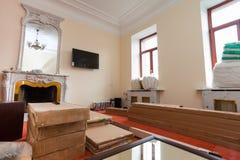 Τα δομικά υλικά, τα έπιπλα, η TV και το τηλέφωνο είναι στο πάτωμα στο διαμέρισμα με την αναδρομική εστία του ξενοδοχείου Στοκ Εικόνες